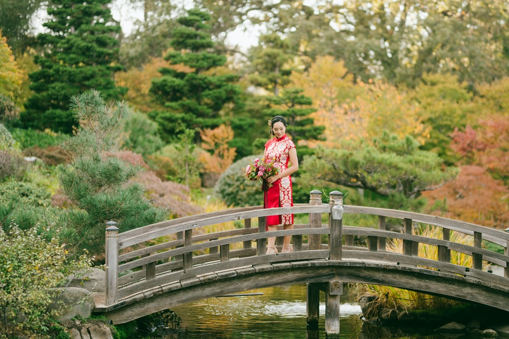 woman in red dress standing on wooden bridge over river during daytime