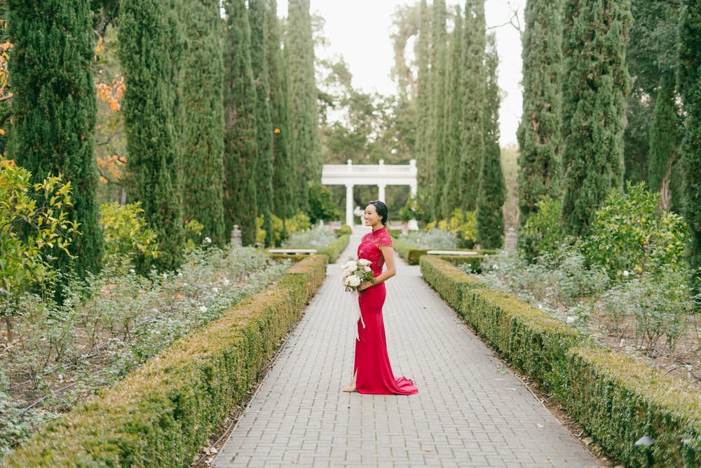 woman in red dress walking on pathway between green plants during daytime