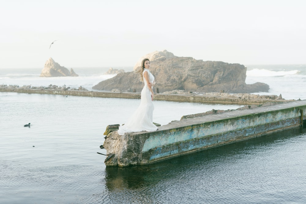 woman in white dress standing on brown wooden dock during daytime