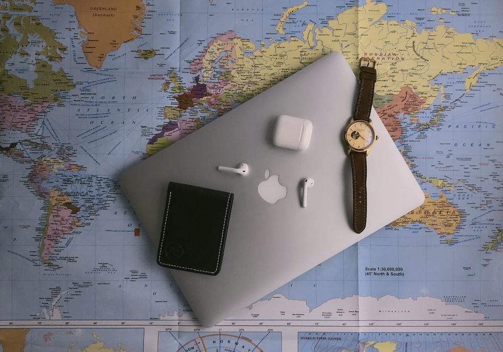 black ipad beside silver round analog watch