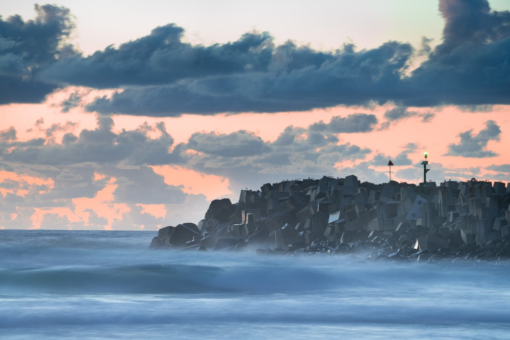 ocean waves crashing on rocky shore under cloudy sky during daytime