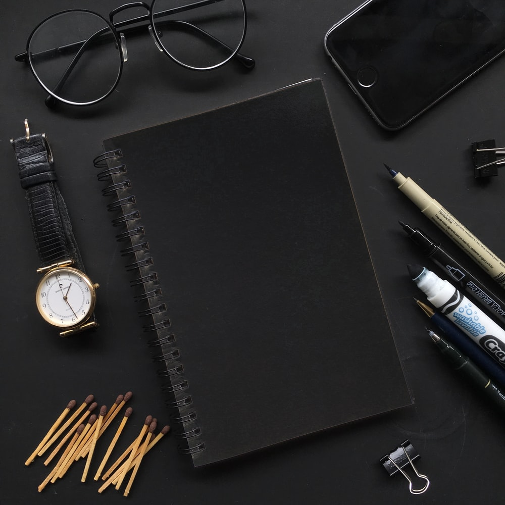 black leather tablet computer case beside silver round analog watch