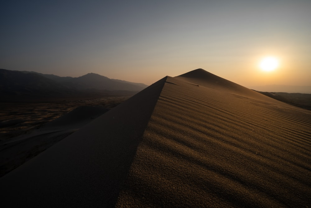 brown sand field during sunset