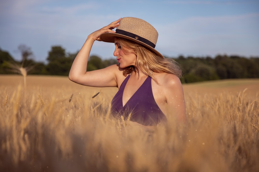 woman in black tank top wearing brown straw hat standing on brown field during daytime