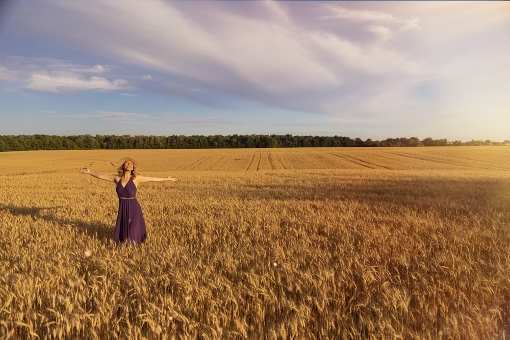 woman in black dress standing on brown grass field during daytime