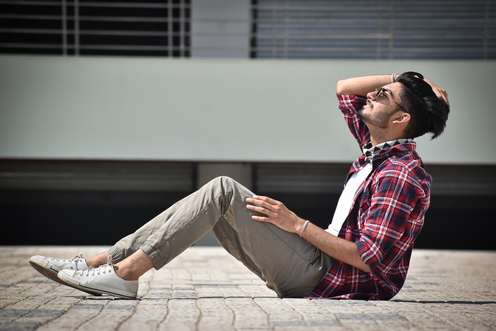 man in red white and blue plaid button up shirt and gray pants sitting on concrete