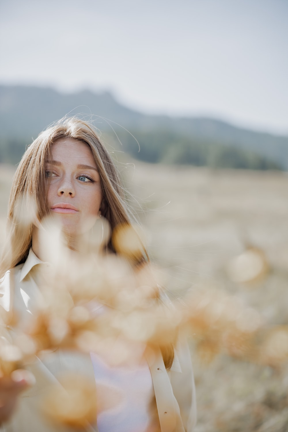 woman in white long sleeve shirt standing on brown grass field during daytime