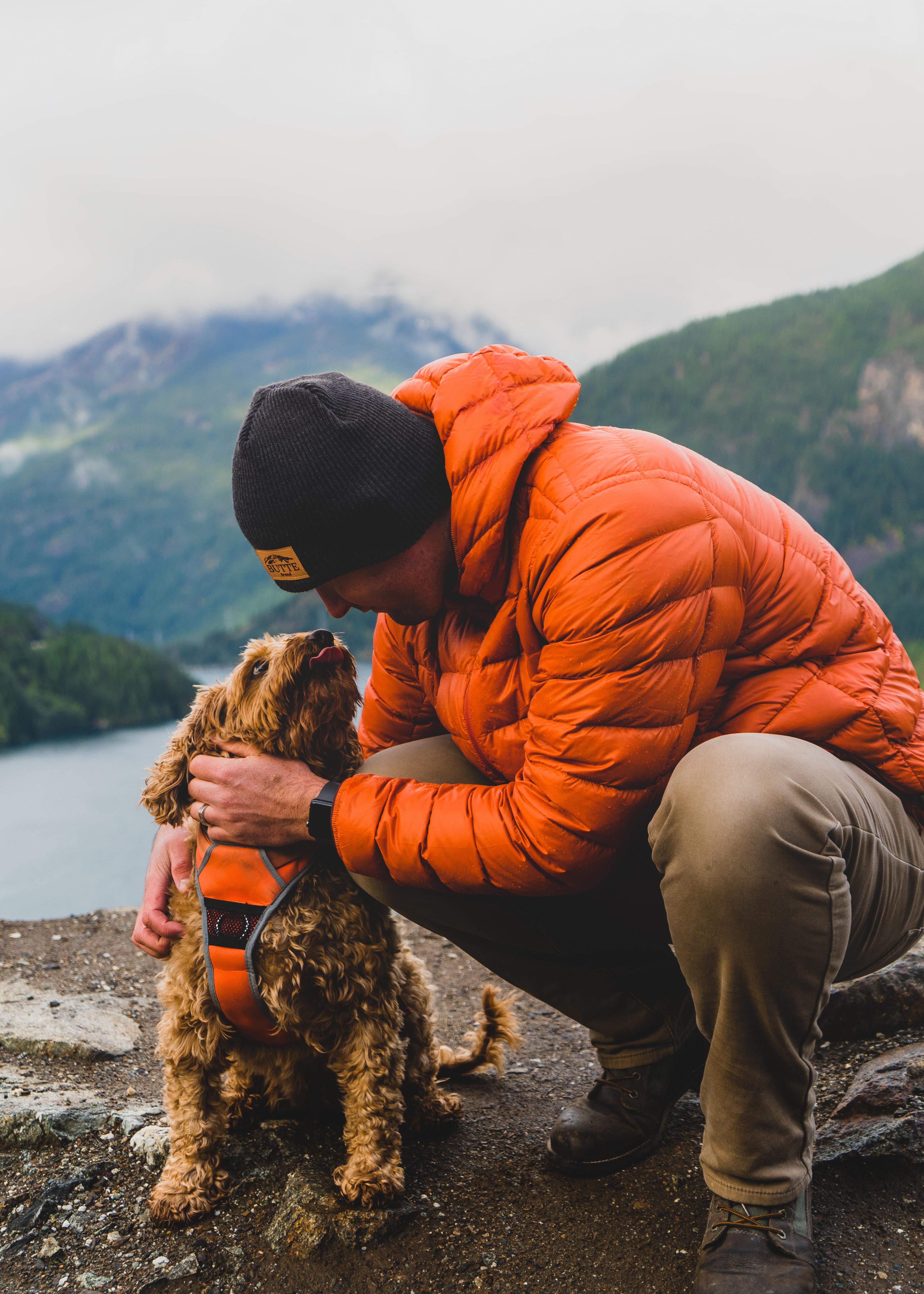 man-in-orange-hoodie-and-black-knit-cap-sitting-on-rock-beside-brown-long-coated-dog