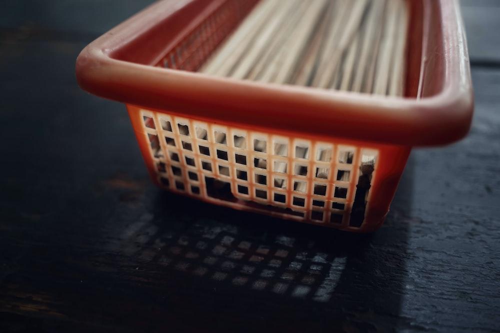 white sticks in orange plastic basket