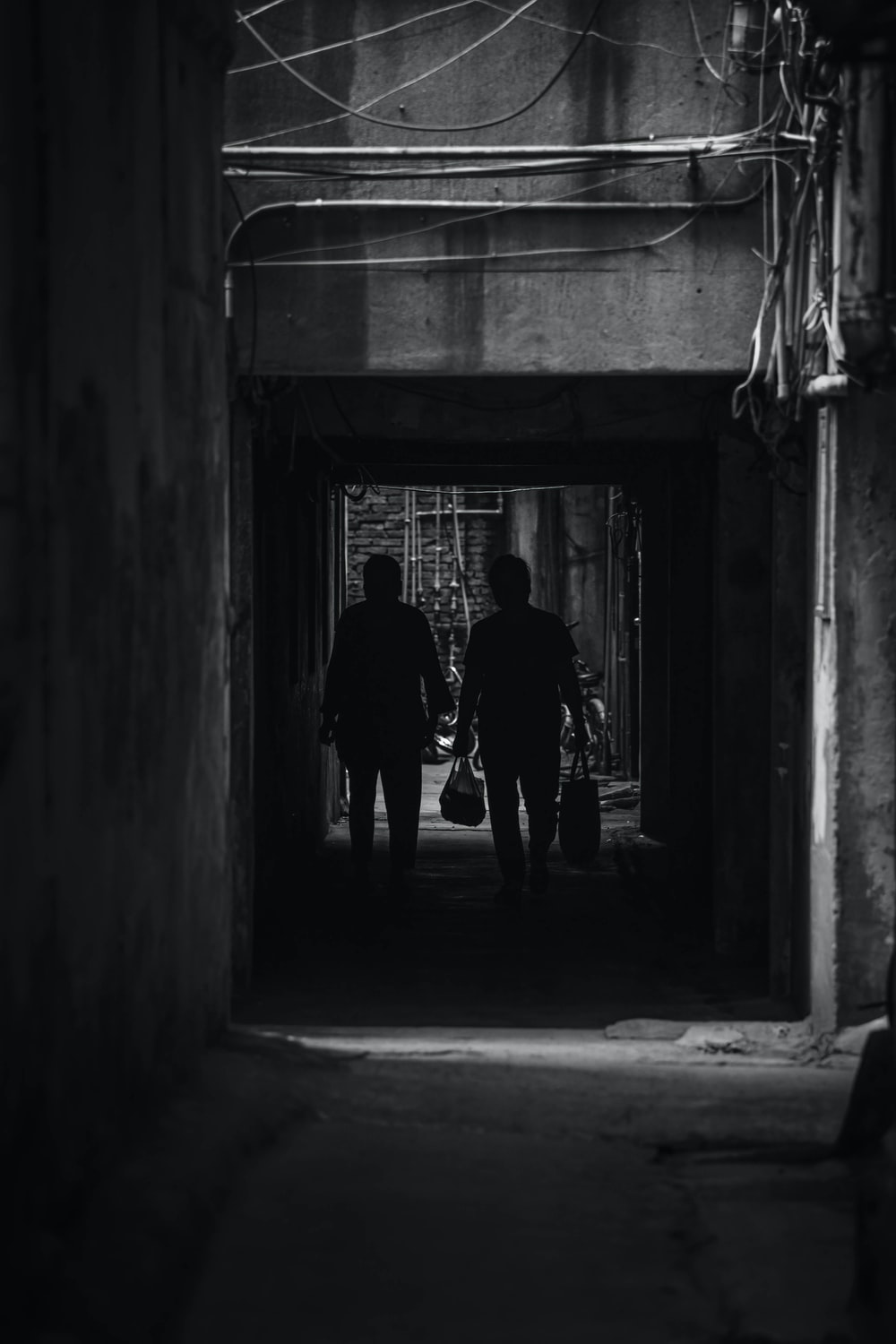 silhouette of man and woman walking on hallway