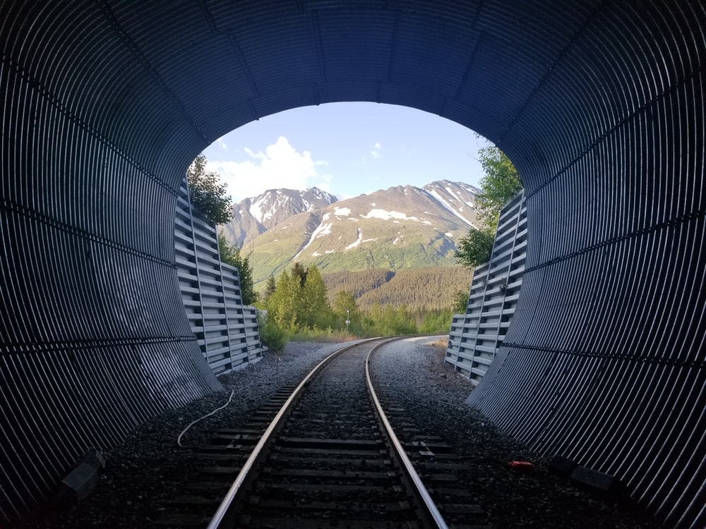 train rail near green grass and mountain during daytime