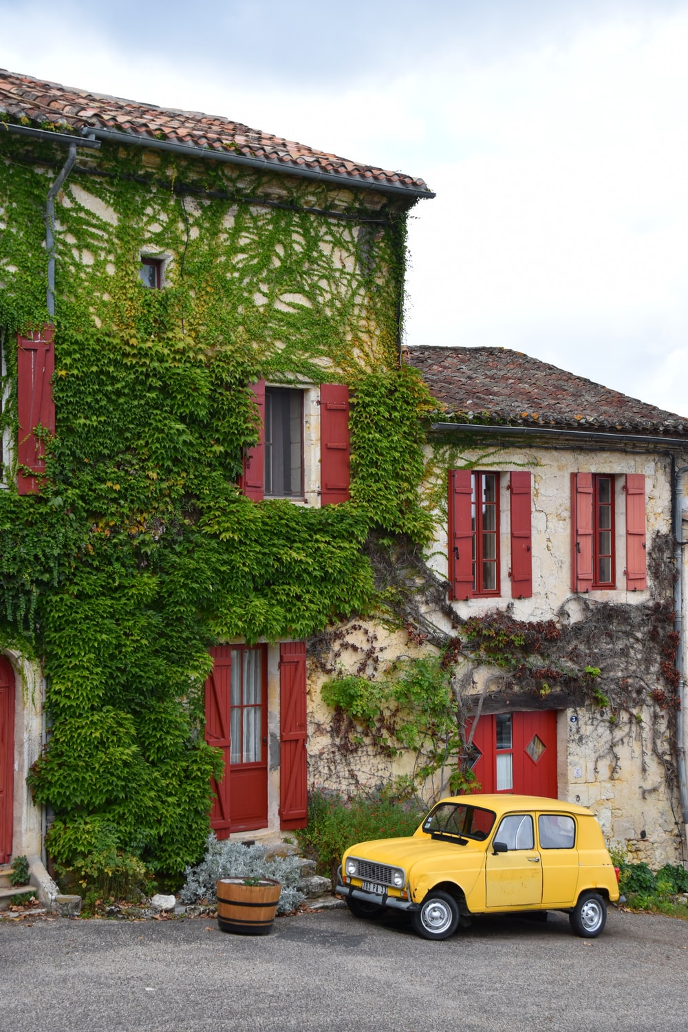 yellow car parked beside red and white concrete building