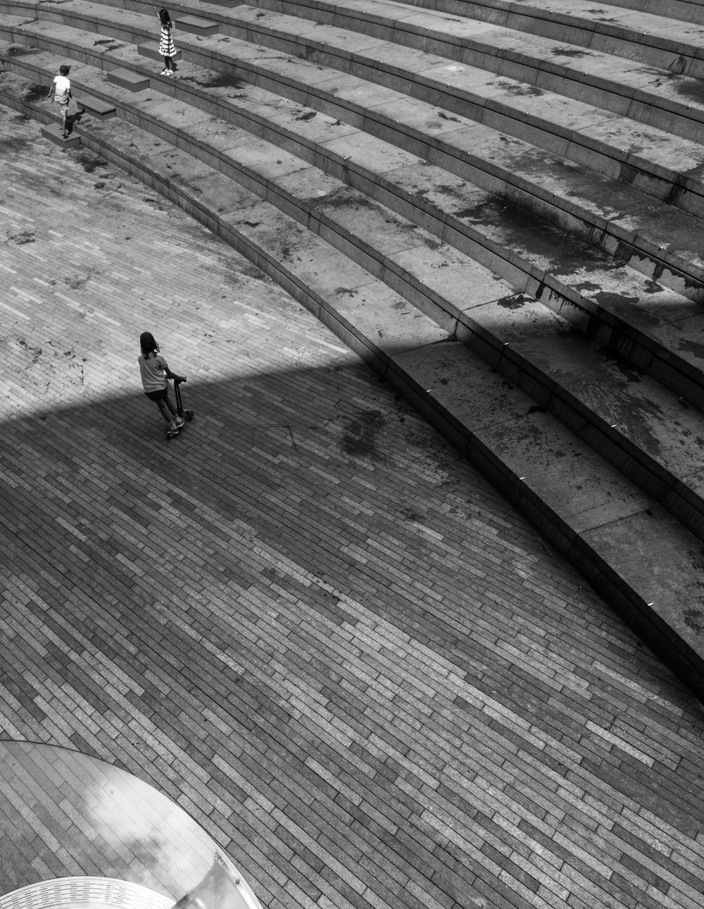 grayscale photo of person walking on concrete stairs
