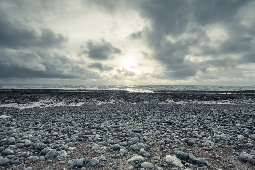 gray and black stones on seashore under gray clouds