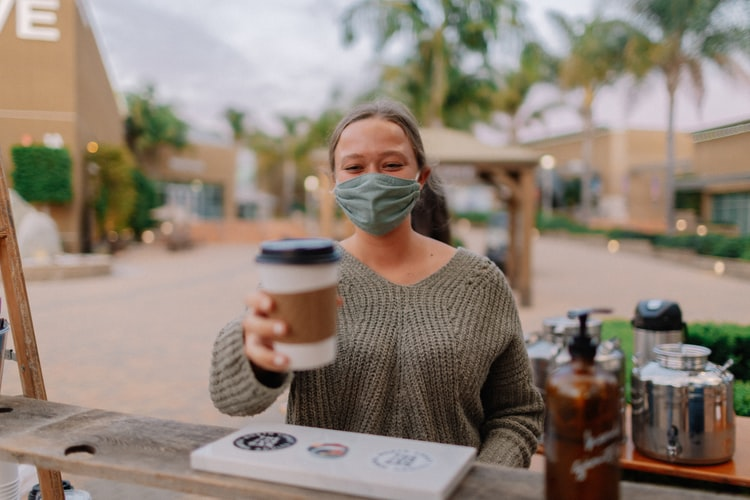 A photo as if the viewer is sitting across the table from a woman who is wearing a health face mask and holding up a coffee cup as if to cheers.
