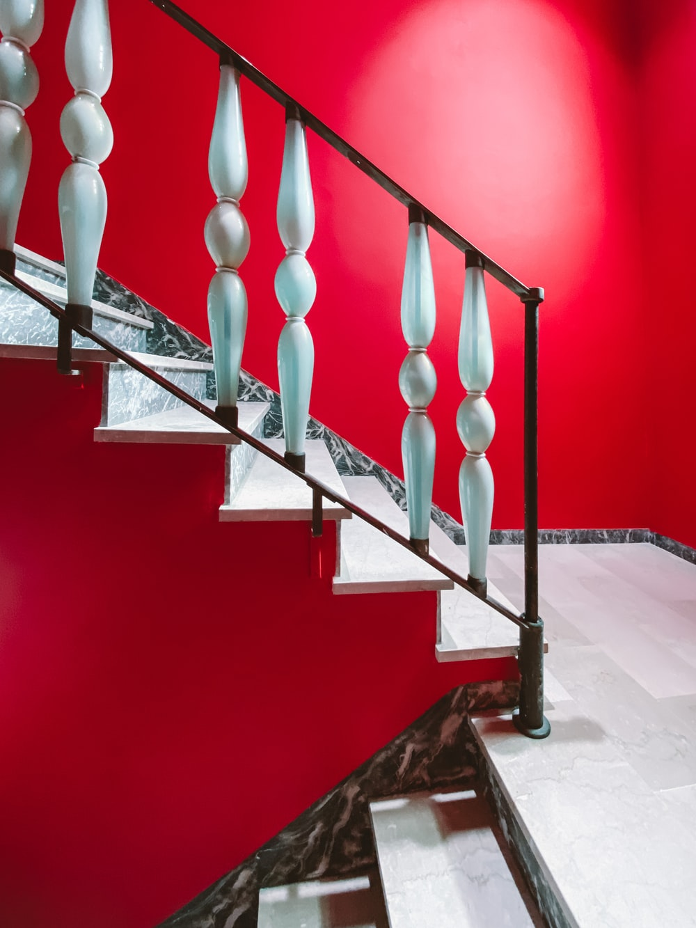 black metal staircase with red wall