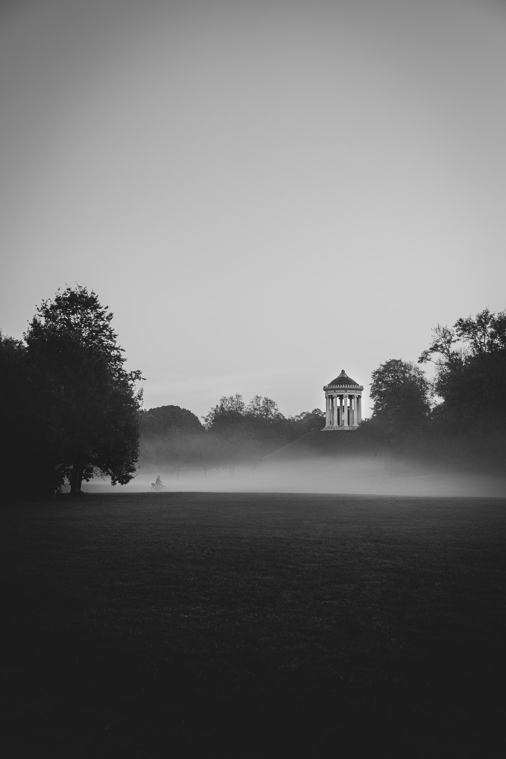 grayscale photo of building surrounded by trees