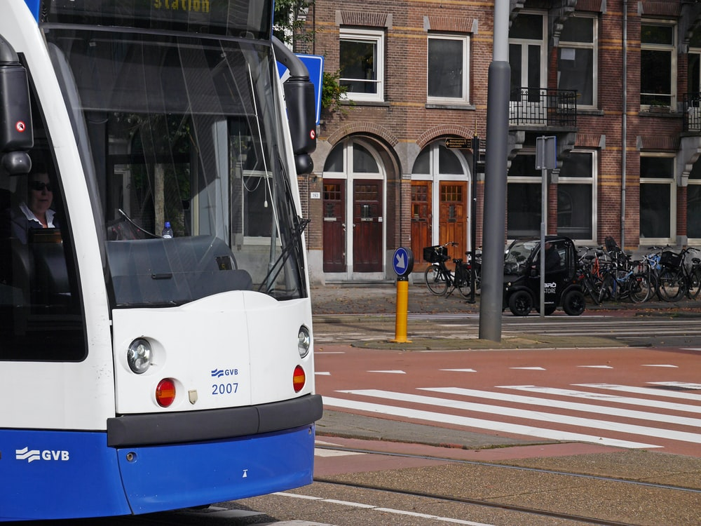 white and blue tram on road during daytime