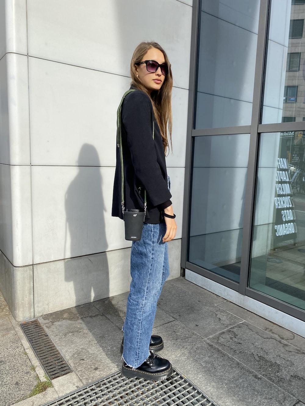 woman in black blazer and blue denim jeans standing near glass window