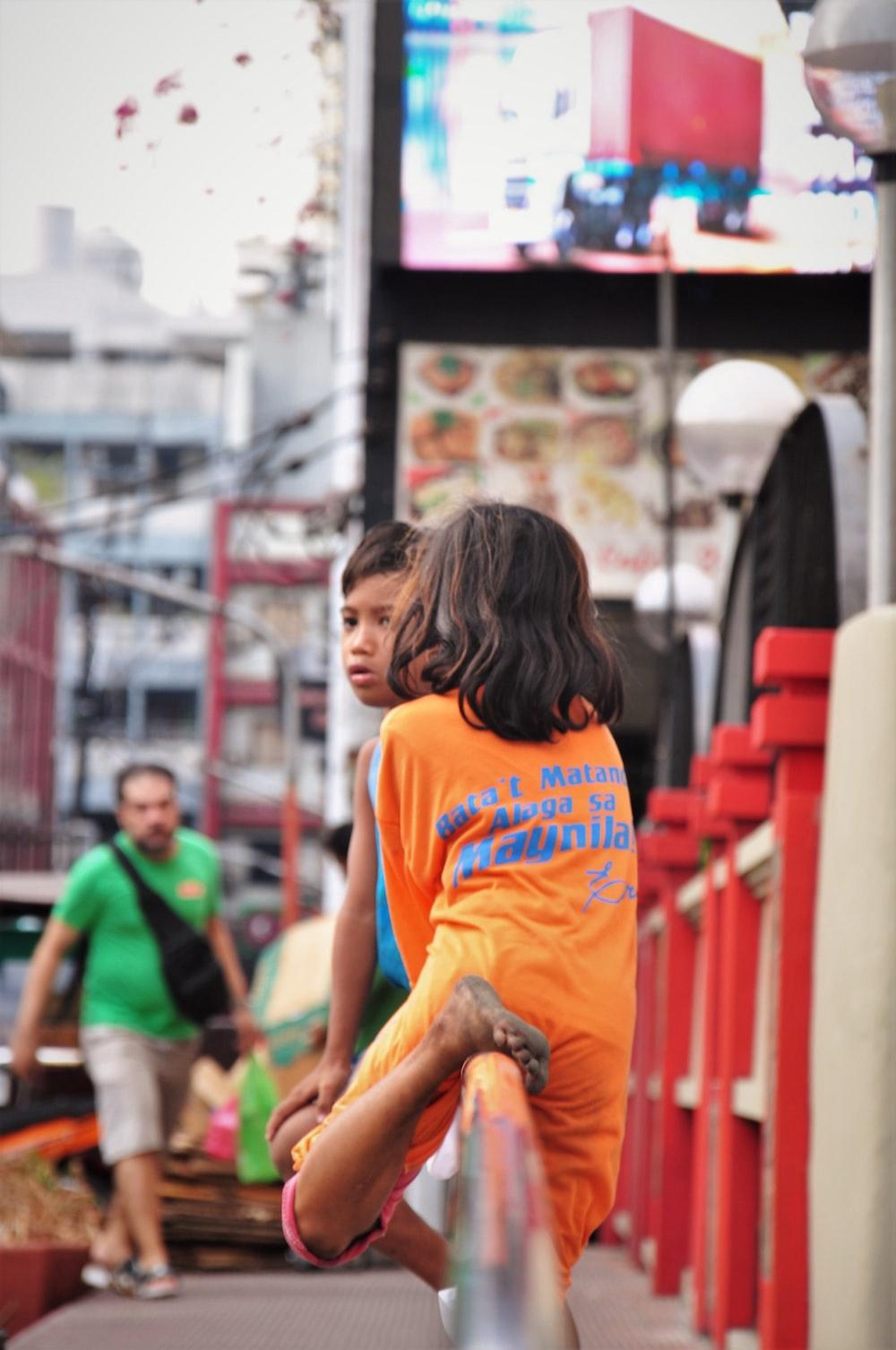 woman in orange crew neck t-shirt sitting on brown wooden bench during daytime