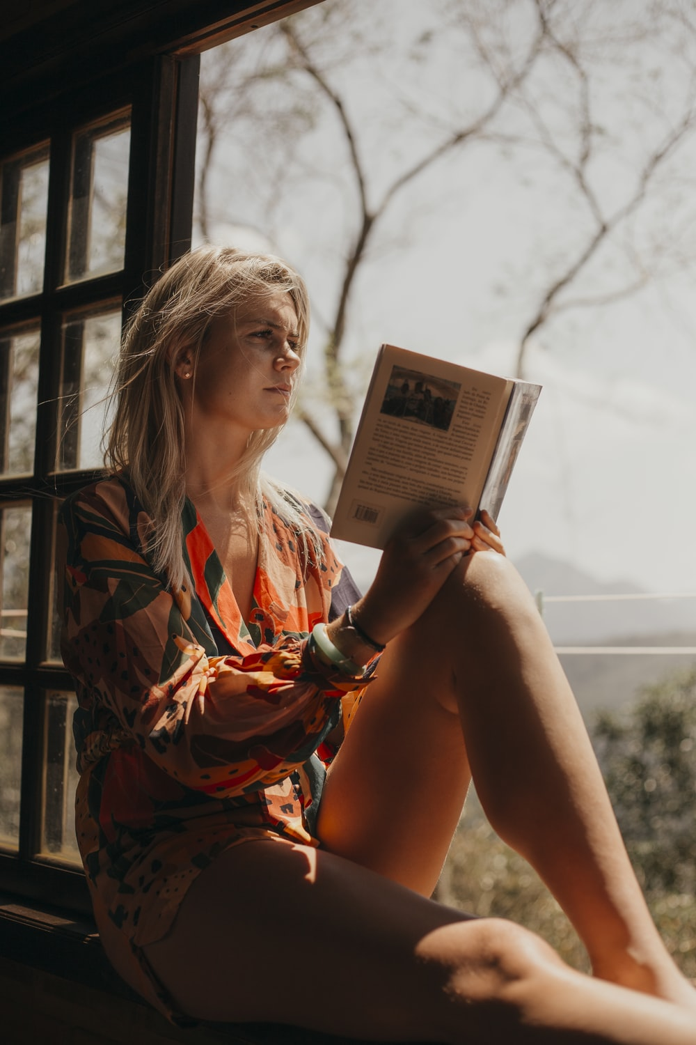 woman in orange and black dress reading book