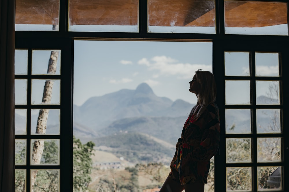 woman in red and black plaid dress shirt standing on window looking at mountains during daytime