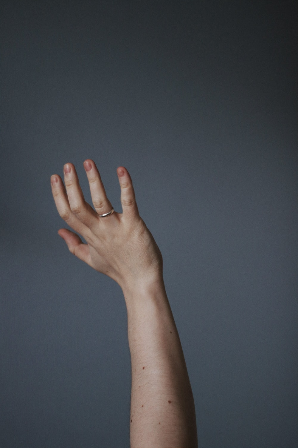 persons left hand on blue wall