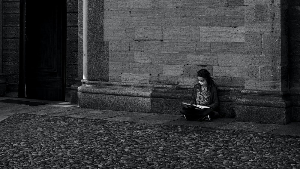 woman in black jacket sitting on concrete bench