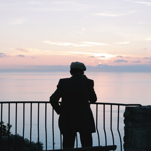 silhouette of man standing near railings during daytime