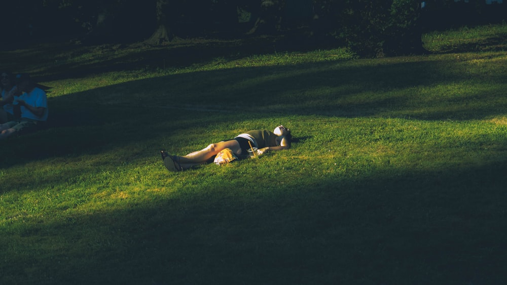 man lying on green grass field during daytime