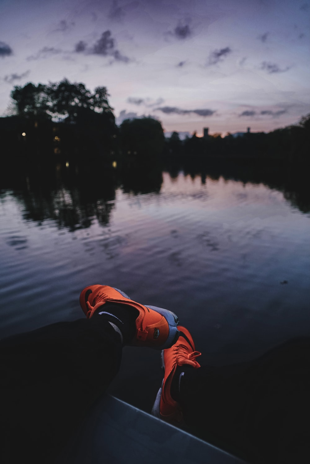 person in black pants and orange shoes sitting on rock in front of lake during daytime
