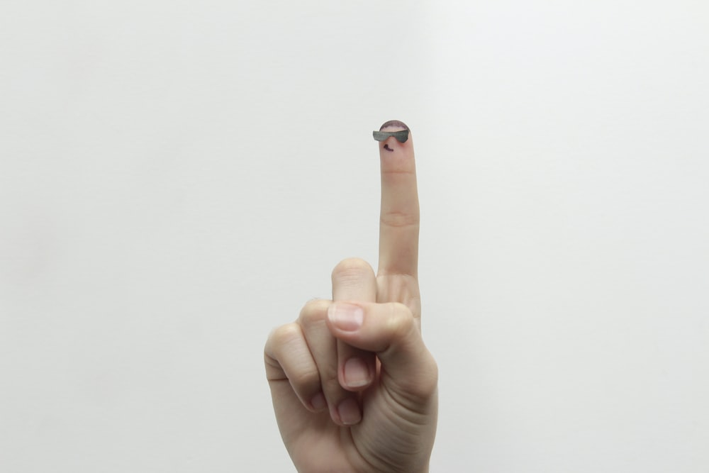 person showing right middle finger