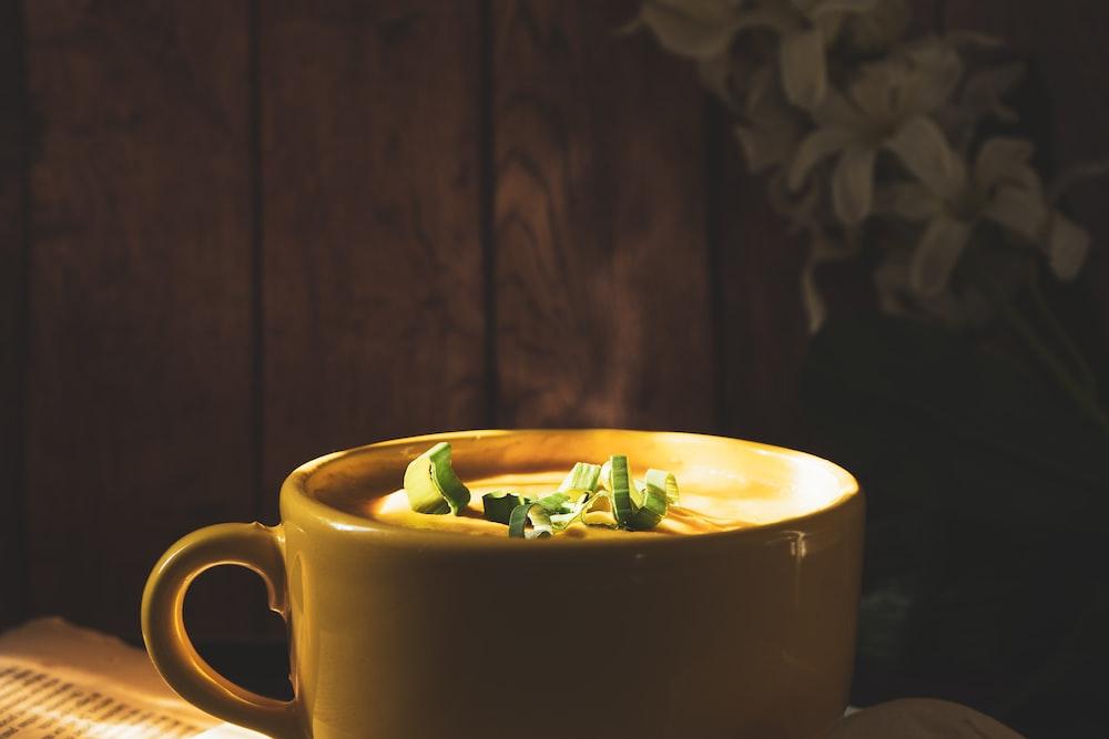 yellow ceramic mug with green leaves