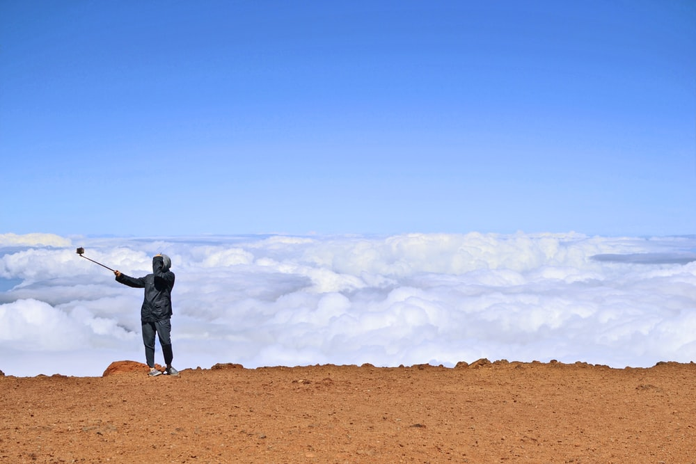 man in black jacket and pants standing on brown field under white clouds and blue sky
