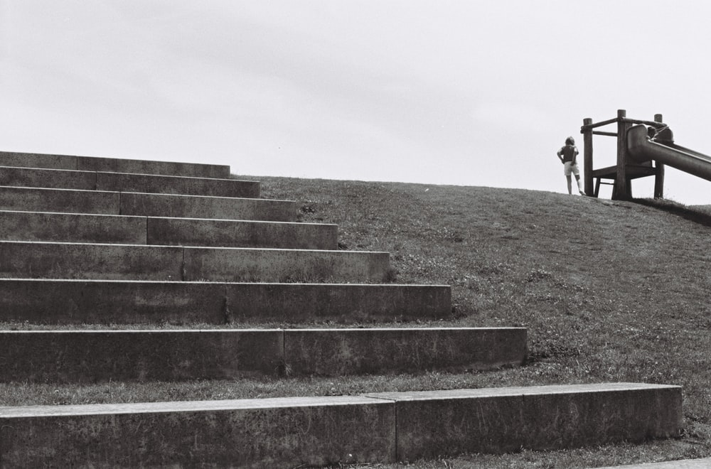 person in black jacket walking on gray concrete stairs during daytime