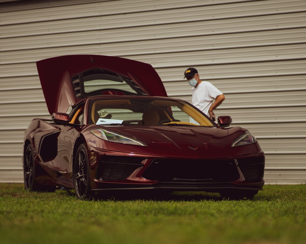 man in white t-shirt and black pants sitting on red ferrari coupe