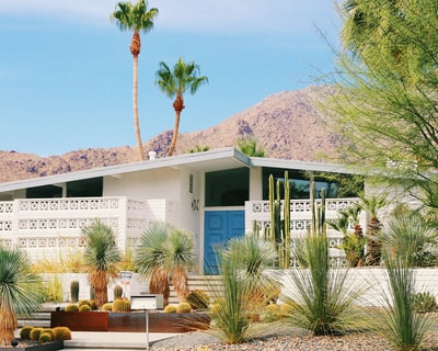 white and blue concrete building near green trees and mountain during daytime midcentury modern teams background