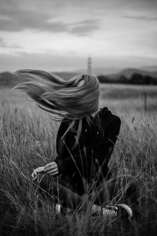 woman in black coat standing on grass field