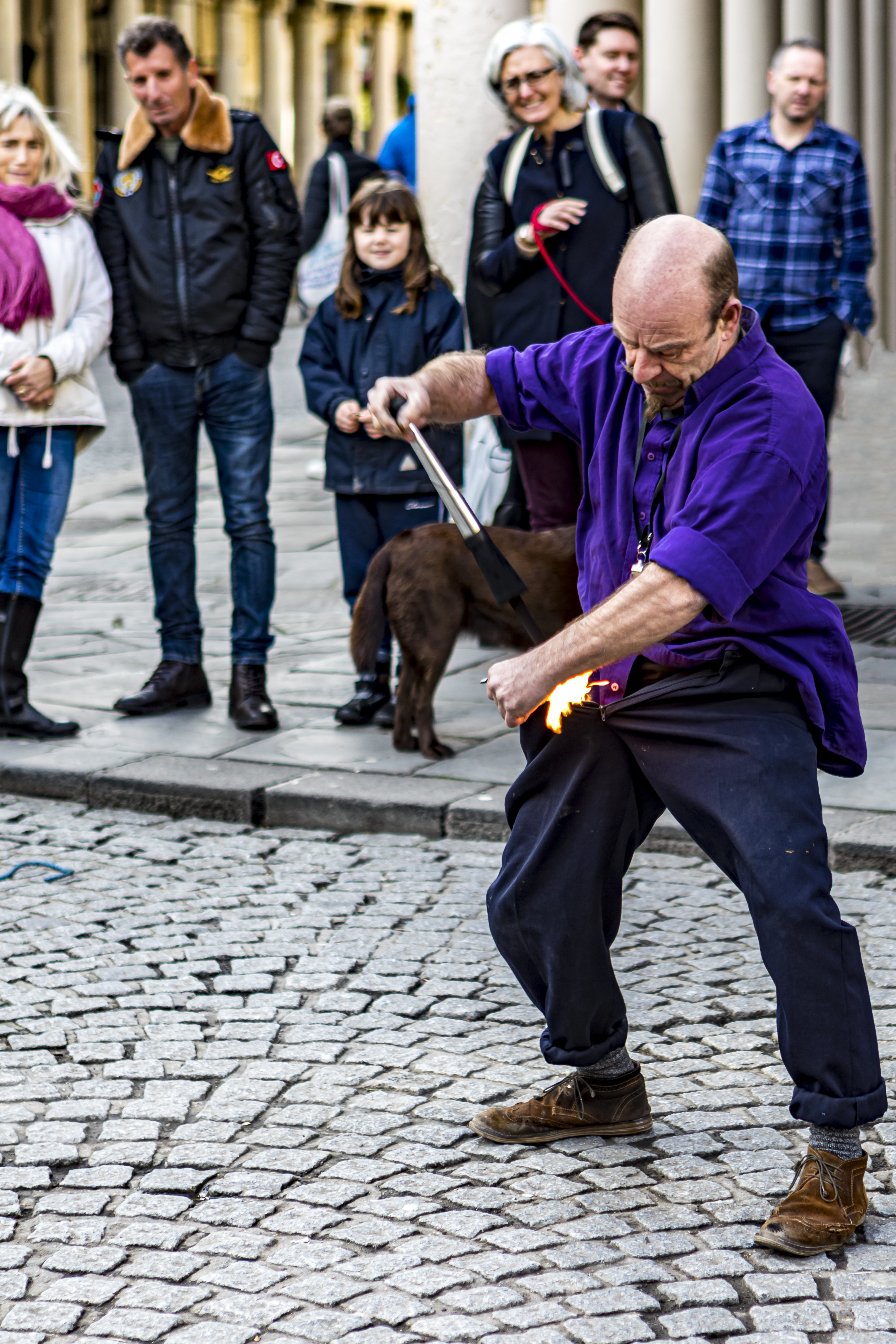 Street performer playing with fire in front of an audience. Bath, England, UK, January 2020.