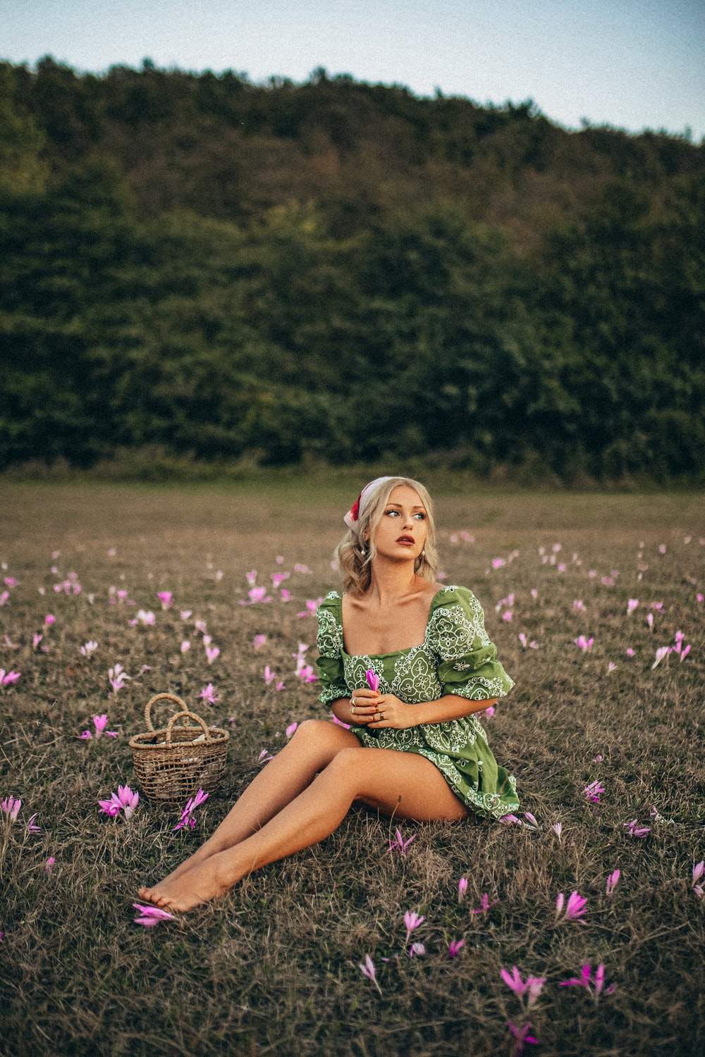 woman in green and white dress sitting on purple flower field during daytime