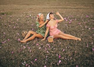 2 women in pink dress sitting on purple flower field during daytime