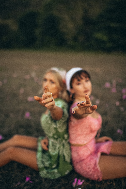 2 girls in green dress holding hands