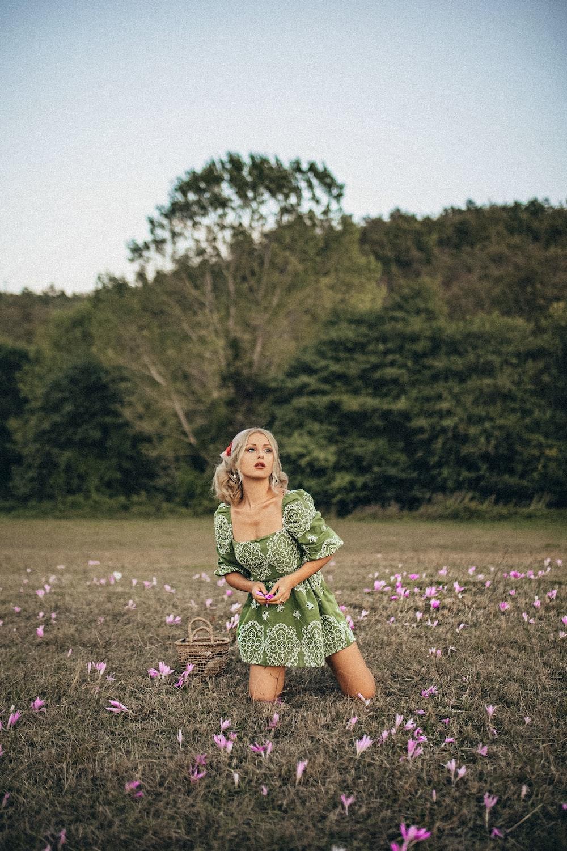girl in green dress standing on purple flower field during daytime