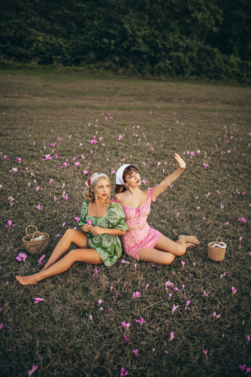 2 girls in pink and green floral dress lying on purple flower field