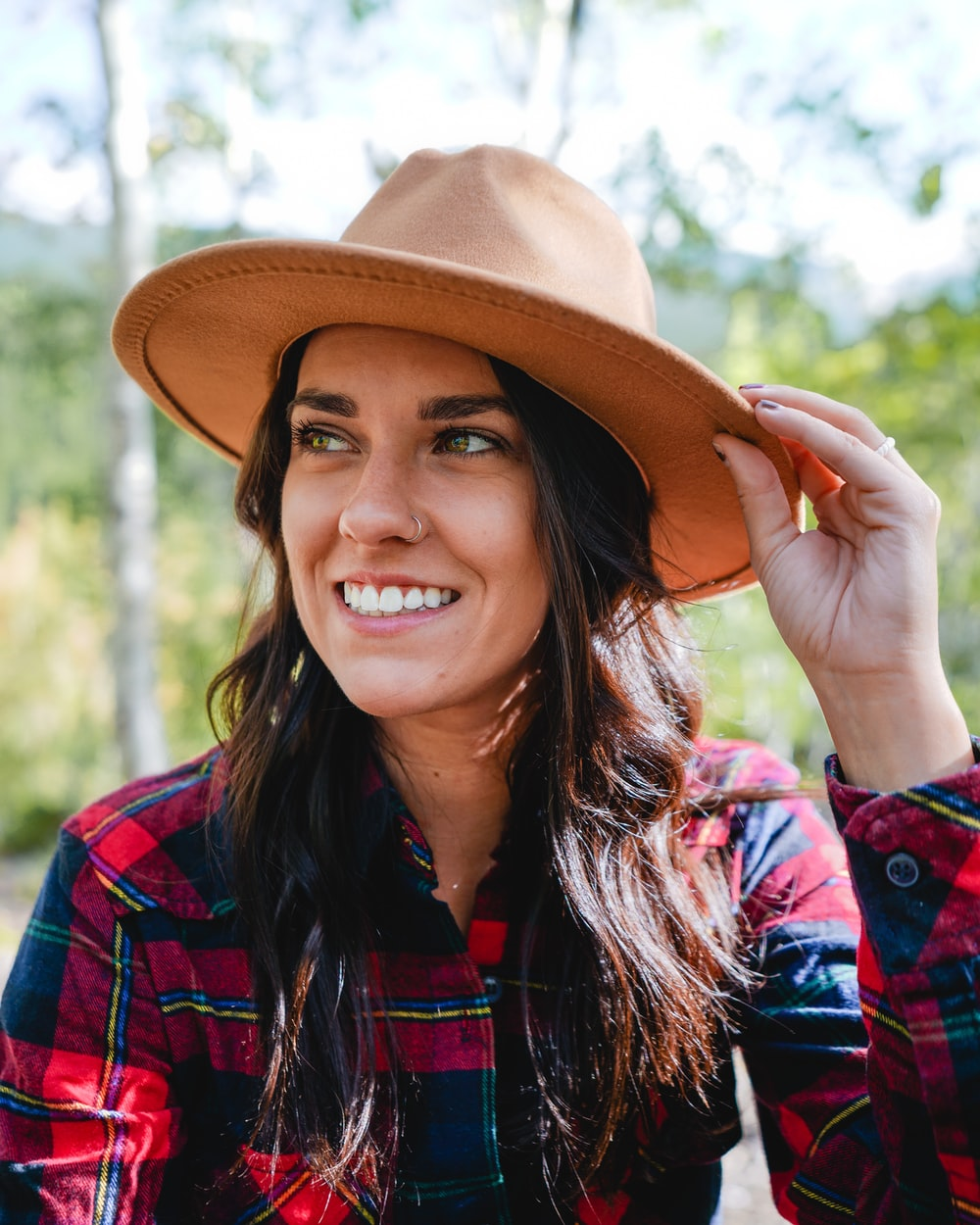 smiling woman in red and blue plaid dress shirt wearing brown hat