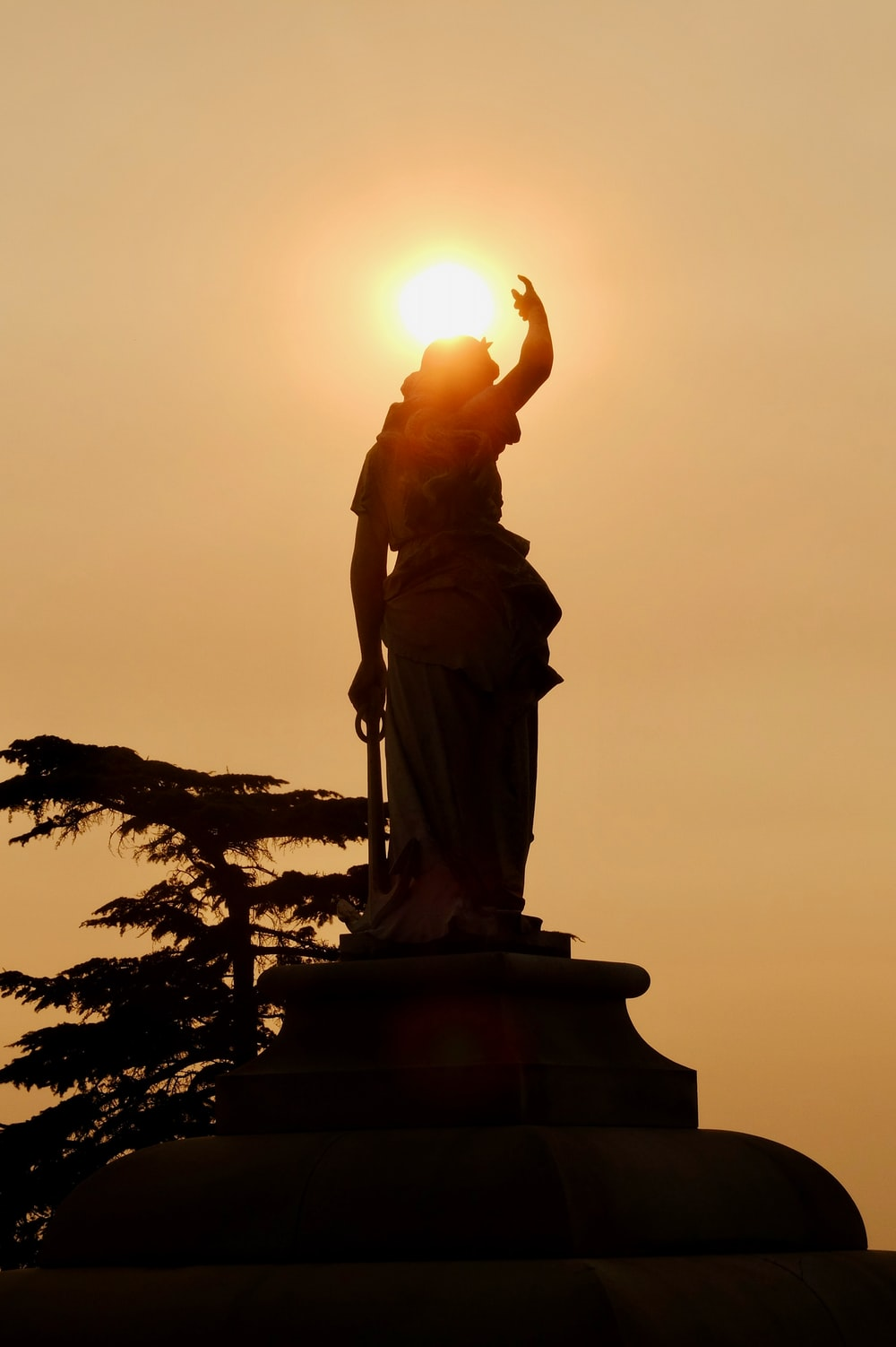 statue of man holding book during sunset