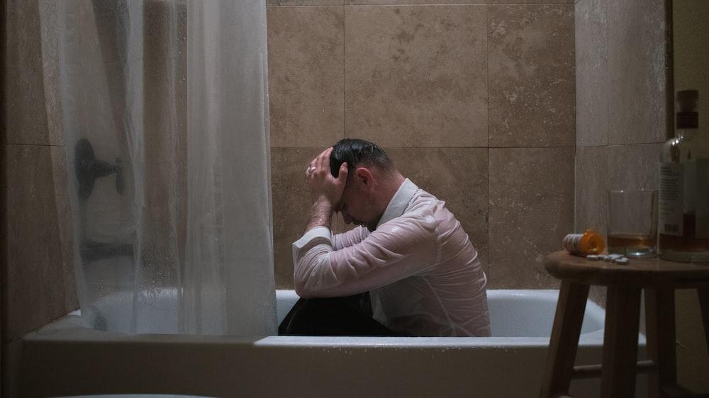 man in white long sleeve shirt sitting on bathtub