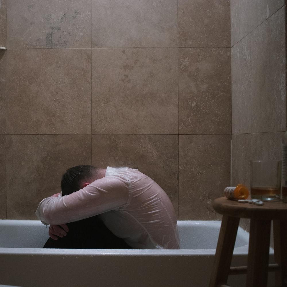 woman in pink long sleeve shirt on bathtub
