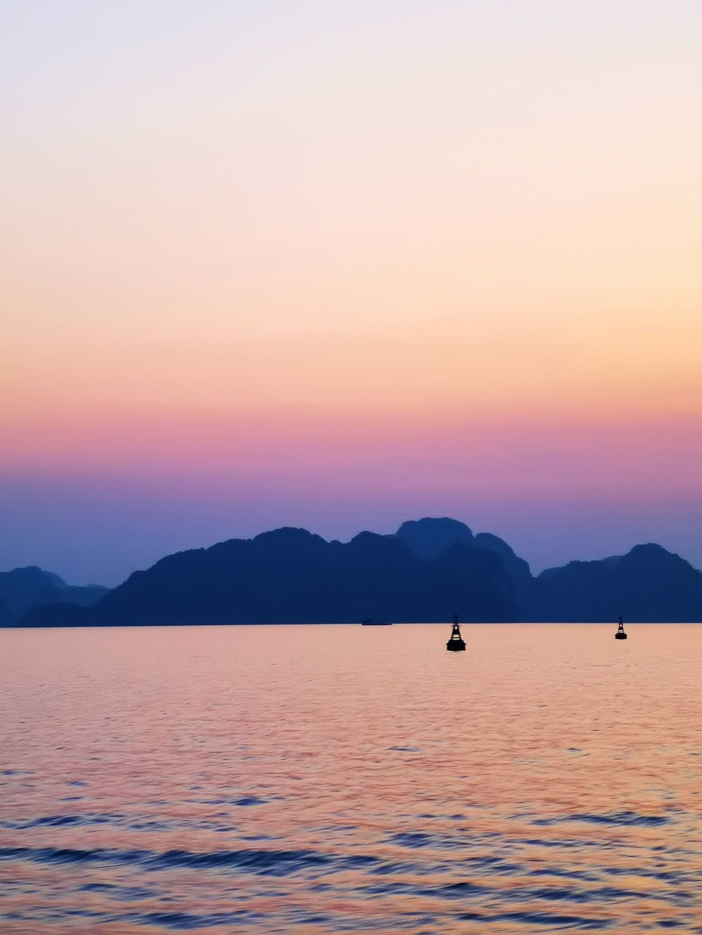 silhouette of person on body of water during sunset