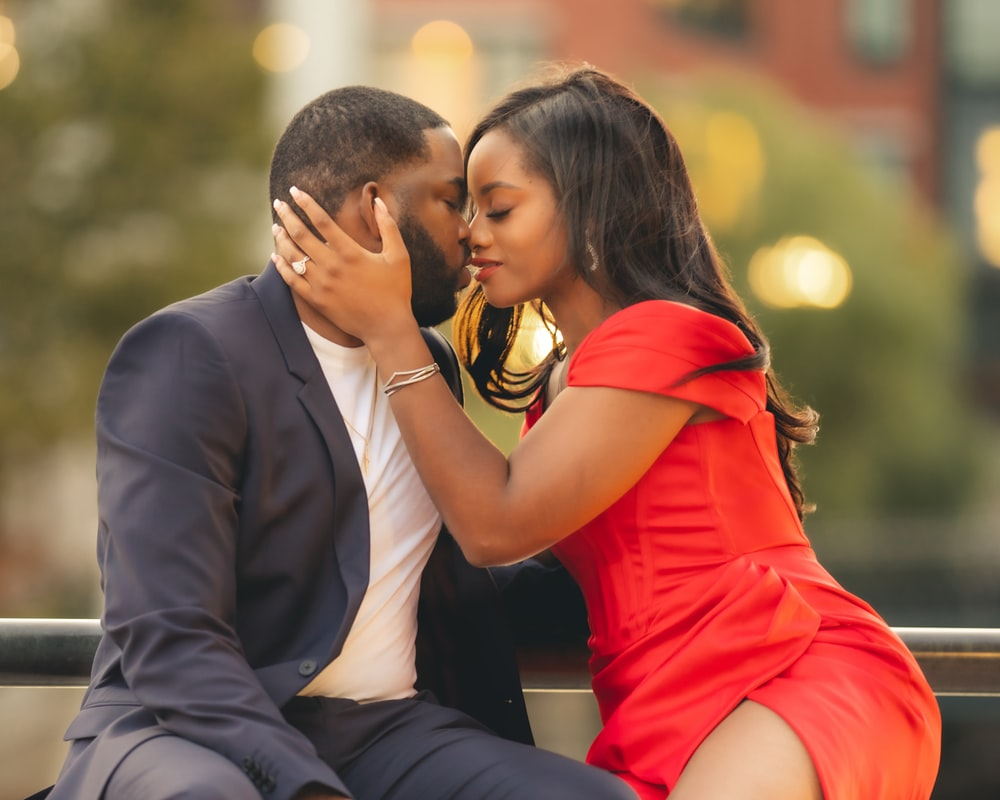 man in black suit kissing woman in red dress